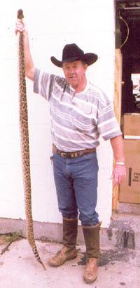 Butch Thompson holding a 7 foot Diamondback Rattlesnake